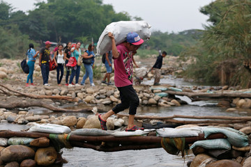 People cross the Tachira river on the Colombian-Venezuelan border, from the outskirts of Cucuta