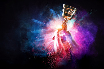 Hands holding champion cup on colourful splashes background. Mixed media