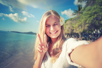 Travel vacation tourist blonde teen girl selfie photo with phone on tropical holiday. summer vacation