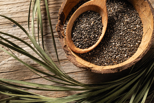 chia seeds in dishes on wooden background, view from above