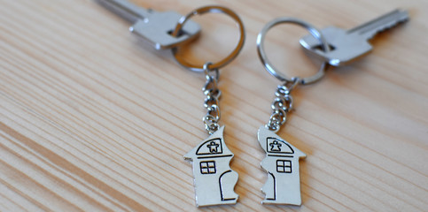 Two keys with splitted or broken key rings with pendant in shape of house divided in two parts on wooden background with copy space. Dividing house when divorce, division of property, real estate heri