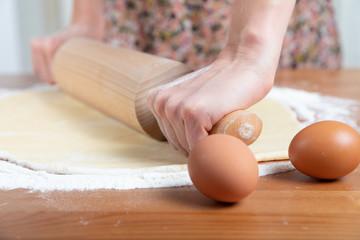 Young beautiful girl making dough