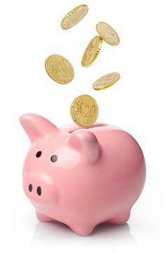 Pink piggy bank with falling coins, isolated on white background