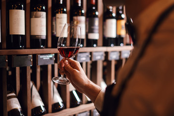 Bartender or male cavist standing near the shelves of wine bottles holds a glass of wine, looks at tint and smells flavor of wine in glass.