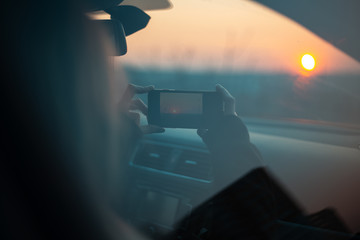 Young girl taking photo of sunset from car.