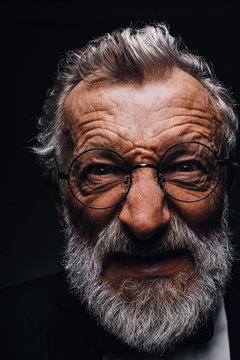 Mature man with angry grimace on face revealing in screwed-up eyes, evil wicked smile and old deep wrinkles close-up. Human emotions and facial expressions concept.