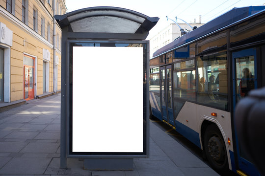 vertical advertising billboard ad in the bus stop. white box for placement in advertising banners. It is located in the city near the road.
