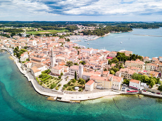 Croatian town of Porec, shore of blue azure turquoise Adriatic Sea, Istrian peninsula, Croatia. Bell tower, red tiled roofs of historical buildings, boat, piers. Euphrasian Basilica. Aerial view