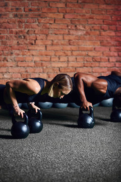 Young caucasian woman athlete doing plank on kettlebells with the help of personal trainer during body core crossfit workout