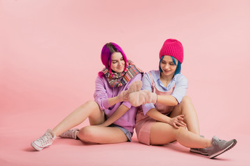 funny awesome girls with mittens on their hands. best lovely women having fun while sitting on the floor.full length photo. best friends support each other in any situation, common ideas and interests