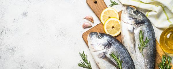 Raw dorado fish on cutting board on the table. Wall mural