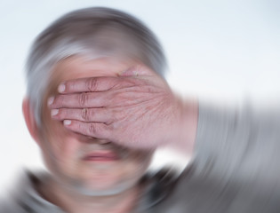 An elderly man is disoriented, he is dizzy, he holds his hand over his eyes. Concept health.