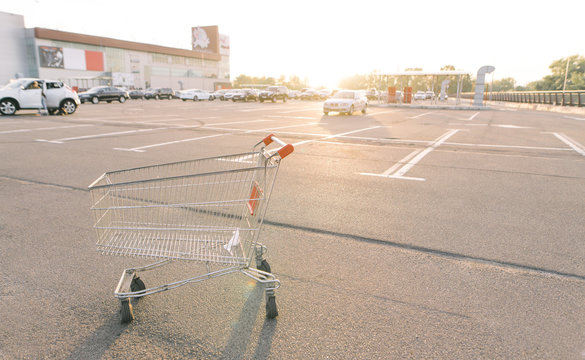 Empty cart for shopping stands in a street parking lot in the center of a shopping mall and in cars. Shopping concept.