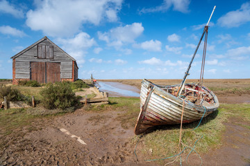 Wall Mural - An old fishing boat under a blue sky at Thornham