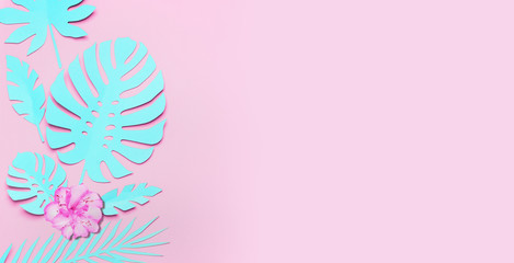 Turquoise tropical leaves and flowers background. Paper tropical leaves on pink background. Creative composing in pastel color with copy space for your design. Banner or template Wall mural