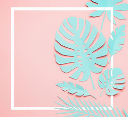 Wall Mural - Turquoise tropical leaves layout. White frame at paper tropical leaves on pink background. Creative composing in pastel color with copy space for your design