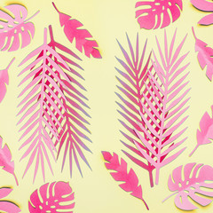 Wall Mural - Pink tropical leaves flat lay on yellow background. Creative layout. Various tropical leaves composing
