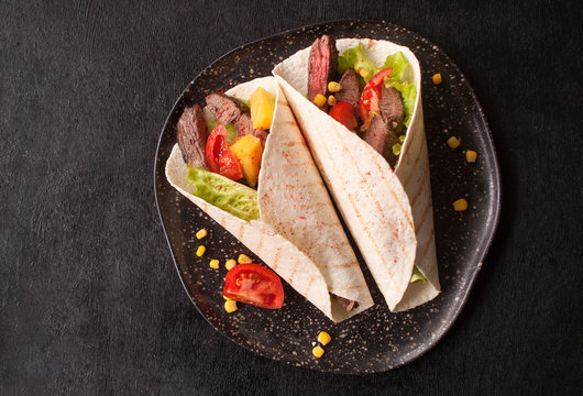 Mexican tacos with beef, vegetables and pineapples and corn grains. Taco al pastor on a wooden Board on a black background. Top view with copy space