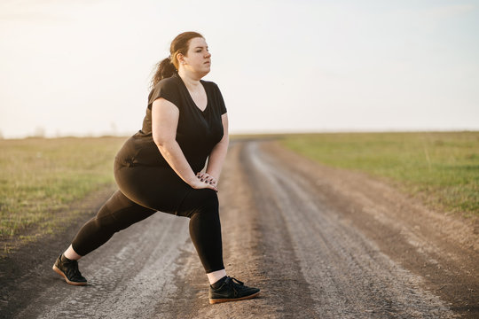 Cropped portrait of woman in sportswear training legs getting ready for running in the meadow, copy space. Healthy lifestyle, sport, weight losing, activity concept