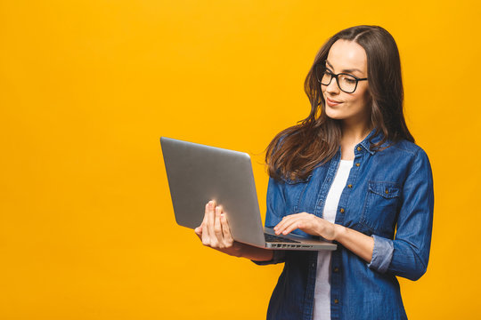 Young happy smiling woman in casual clothes holding laptop and sending email to her best friend. Isolated against yellow background.