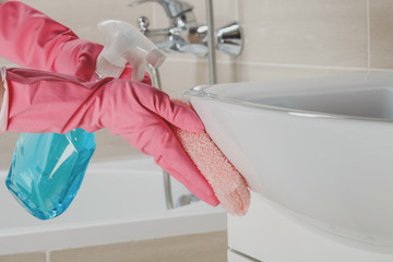 Housemaid in the rubber gloves cleaning bathroom with a sponge