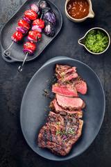Gegrilltes dry aged Wagyu Bürgermeister Steak aufgeschnitten mit Tomaten Zwiebel Grillspieß und scharfer Sauce als Draufsicht auf einem Modern Design Teller