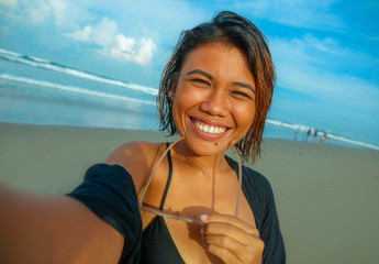young happy and attractive Asian exotic woman on the beach taking selfie portrait with mobile phone smiling cheerful enjoying holidays trip at beautiful tropical island