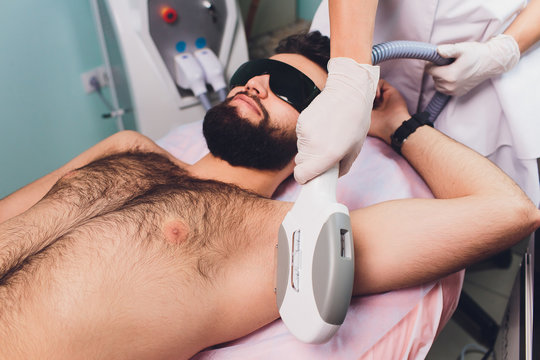 Men lying at beautician's during laser armpit hair removal therapy.