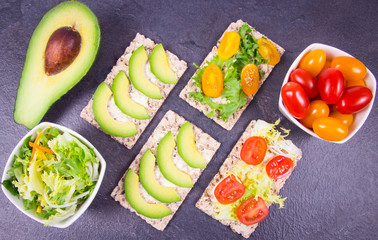 Healthy snack from wholegrain rye crispbread cracker with cherry tomatoes, avocado and salad. Proper nutrition.