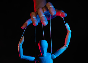 Concept of control. Marionette in human hand. Objects are colored on red and blue light.