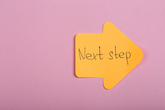 """Business, future and motivation concept - orange sticker in the shape of an arrow and text """"Next step"""" on pink background"""