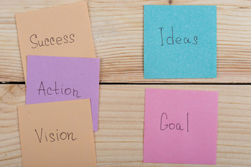 Business and success concept - colorful sticky notes with words success, action, goal, vision, idea