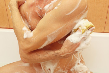 Attractive man lathers sponge body in the bath close up Wall mural