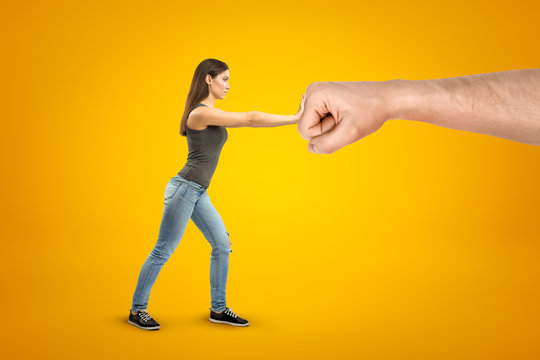Young brunette girl wearing casual jeans and t-shirt making stop gesture against big male stretched fist on yellow background