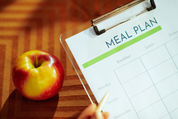 Closeup on meal plan and apple in modern living room