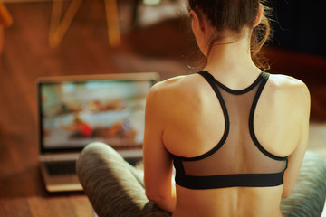 sports woman and using online fitness training program in laptop