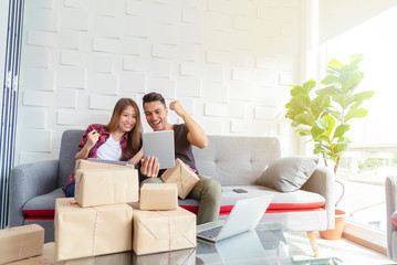 Couple happy after successful online selling at home. Small business with technology concept.