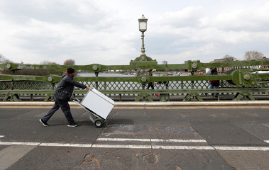 A man wheels an appliance across Hammersmith Bridge following its' closure to traffic caused by critical faults in London