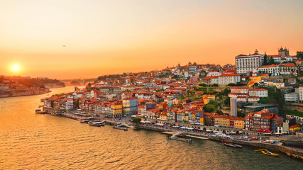 Beautiful skyline of portuguese city Porto taken during amazing sunset. Captured on 16:9 picture. The city center and the Porto Cathedral are in orange sunset light.