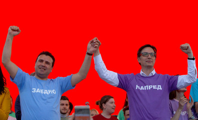 Macedonian Prime Minister and leader of the ruling SDSM, Zoran Zaev, and presidential candidate Stevo Pendarovski greet their supporters during a party meeting in Skopje