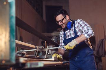 Carpenter doing his job in carpentry workshop
