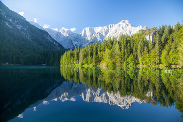 Beautiful morning scene with alpine peaks reflecting in tranquil mountain lake