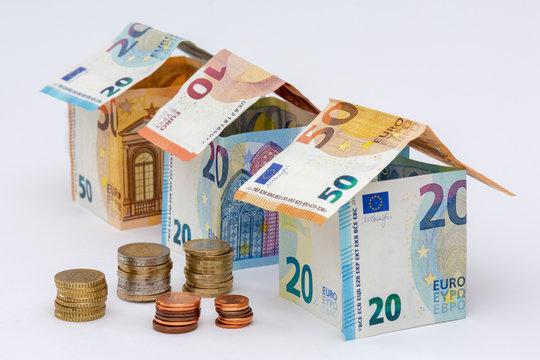Trois maisons faites en billets de 10, 20, et 50 euros, avec quelques pièces de monnaie
