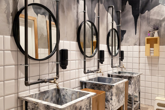 Russia Novosibirsk 2018-11-18 Modern interior of restaurant loft style toilet, square concrete sinks, copper faucet, black industrial pipes, round mirror belt on wall with white tiles