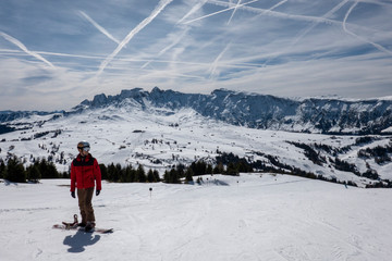 Snowboarder with red jacket in front of Dolomites mountains in Seiser Alm