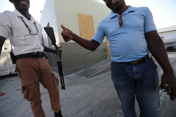 A security guard reacts next to a local resident while guarding a vandalized gasoline station after a looting during anti-government protests in Port-au-Prince