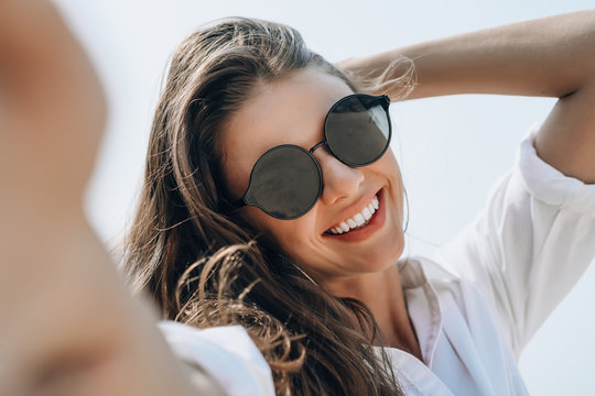 Close-up of young beautiful woman in sunglasses smiling holding camera and smiling while taking selfie on the beach.Woman enjoying summer vacation concept.