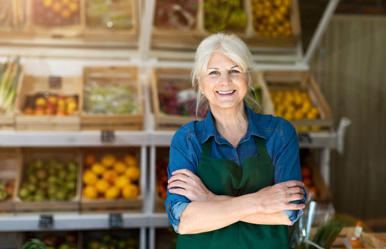 Portrait of confident owner with arms crossed standing in small grocery store