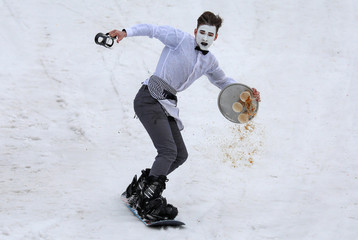 Snowboarder in a festive costume glides down while competing in the annual Gornoluzhnik amateur event in Krasnoyarsk