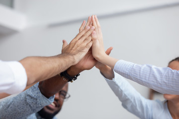 Multi ethnic business team give high five together, close up